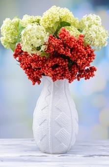 Flores e frutas em um vaso, na mesa de madeira,
