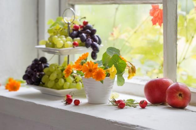 Flores e frutas no peitoril da janela