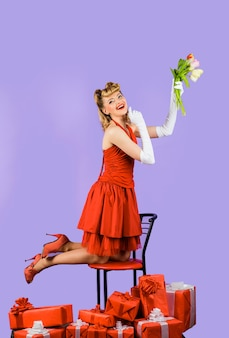 Flores e mulher retrô com caixa de presente e flores sorrindo mulher retrô segurando flores da primavera