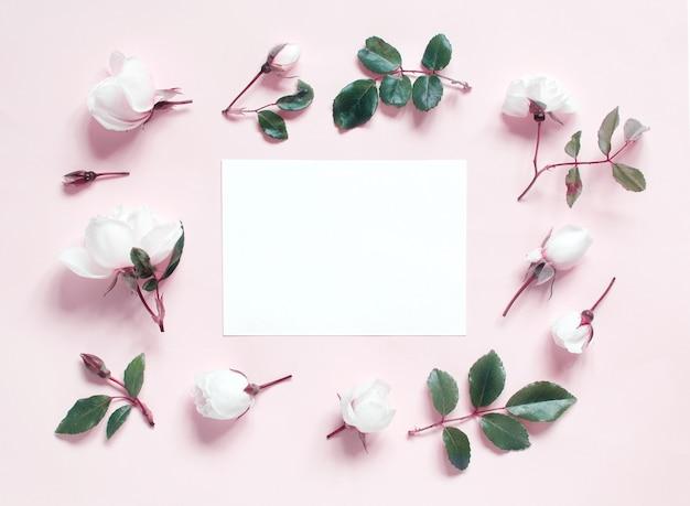 Flores e papel em uma vista superior rosa claro retrô