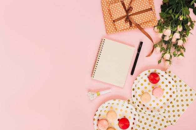 Flores e presente perto de notebook e macaroons