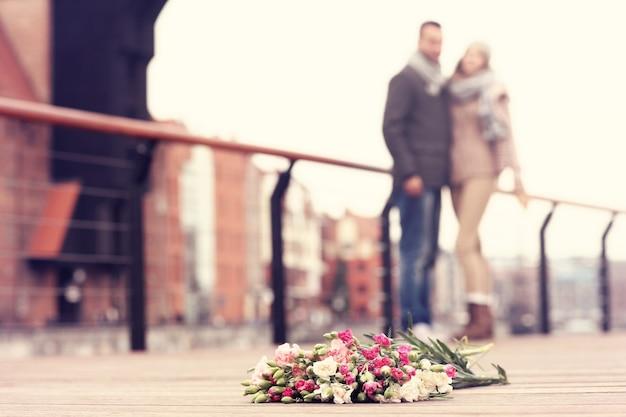 Flores e um casal se abraçando no fundo