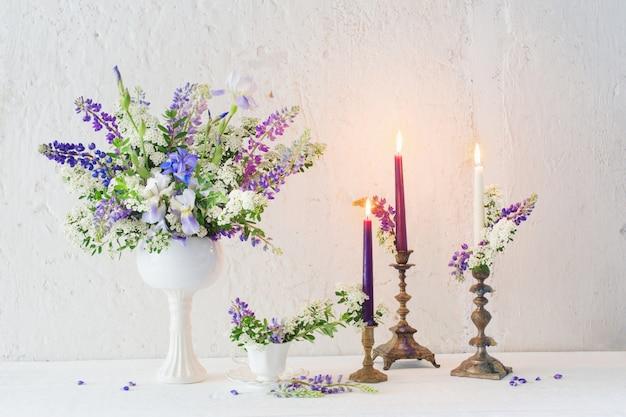 Flores e velas na parede do fundo branco