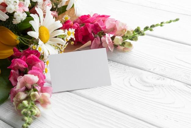 Flores em ângulo alto com cartão em branco