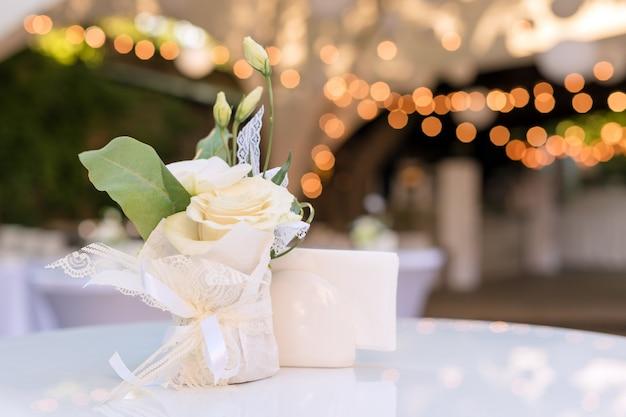 Flores em cima da mesa no restaurante ao ar livre. interior de um terraço de verão do café. cenário de mesa para recepção de casamento ou um evento. copie o espaço para texto.