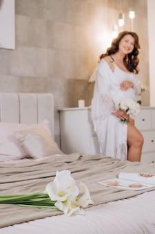 Flores em foco mulher grávida em um hotel com uma túnica branca publicidade clínica