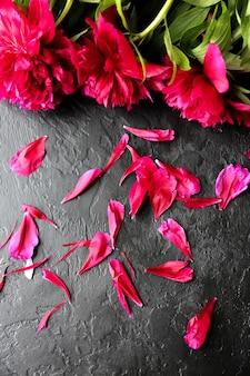 Flores em fundo preto. buquê de peônias. plano perfeito com pétalas. cartão postal de férias de mães felizes. saudação do dia internacional da mulher. ideia de aniversário para anúncio. convite.