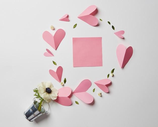 Flores em um balde, corações de papel e cartão de dia dos namorados em branco com espaço de cópia