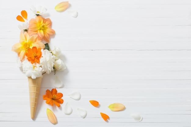 Flores em um cone de waffle na mesa de madeira branca