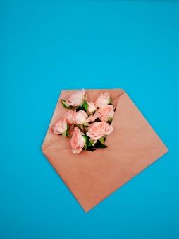 Flores em um envelope kraft, cópia espaço, fundo azul