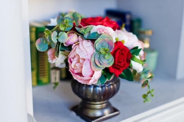 Flores em um vaso antigo na prateleira com livros