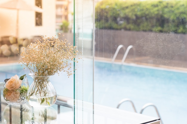 Flores em um vaso colocado ao lado do copo à beira da piscina