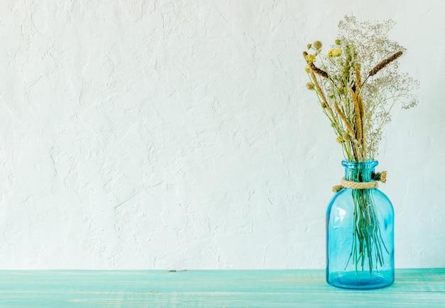 Flores em um vaso em cima da mesa.