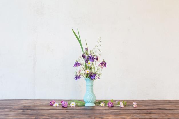 Flores em um vaso na mesa de madeira na parede do fundo branco