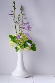 Flores em um vaso sobre uma mesa de madeira branca. manhã, natureza-morta rústica.
