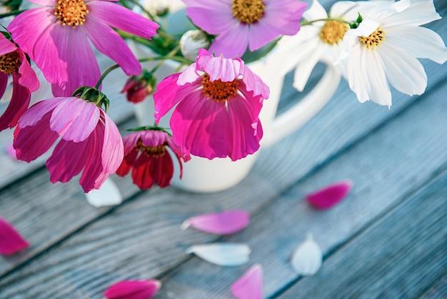 Flores em uma caneca, pétalas na mesa de madeira