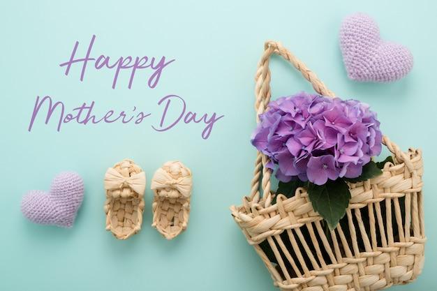 Flores em uma cesta de palha em azul, texto feliz dia das mães.