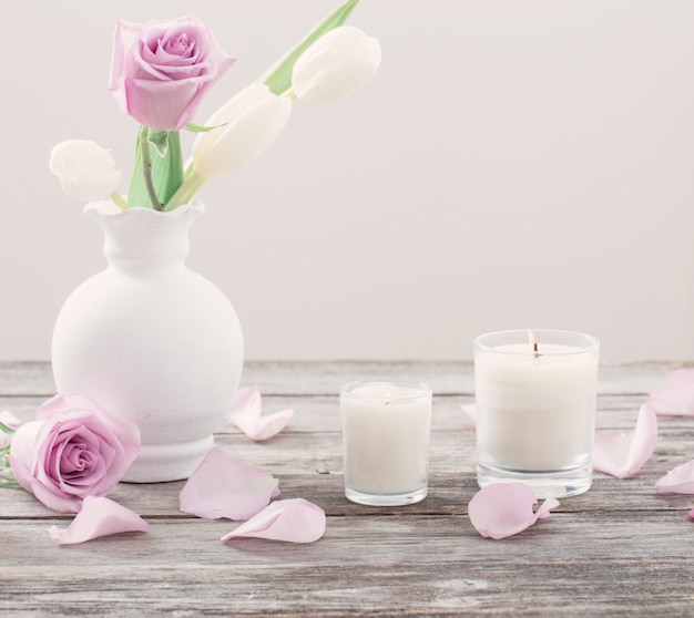 Flores em vaso com vela perfumada