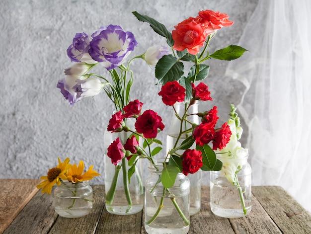 Flores em vasos de garrafa em uma mesa de madeira
