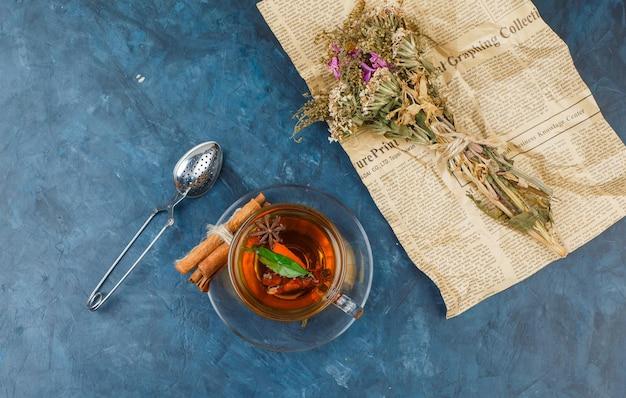 Flores embrulhadas em jornal com uma xícara de chá, canela e um coador de chá