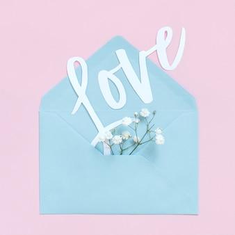 Flores, envelope e a palavra amor em uma vista superior do plano de fundo rosa claro