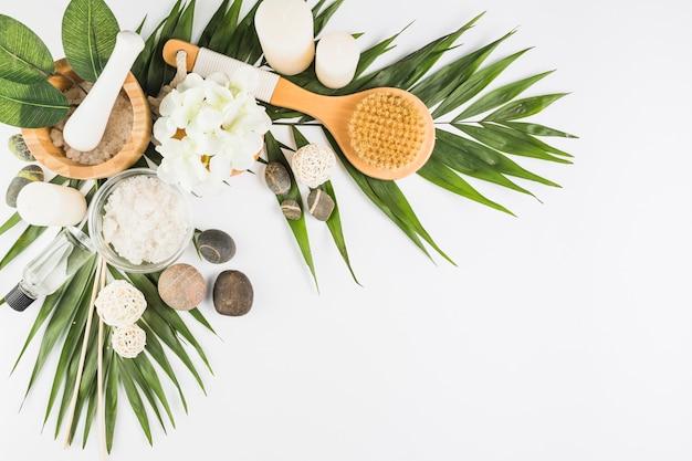 Flores; escova; pedras de spa; sal; velas; garrafa de óleo na superfície branca