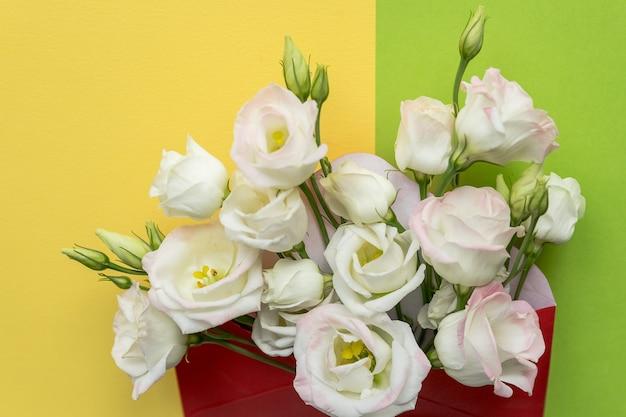 Flores eustoma com envelope na superfície colorida. envelope aberto com arranjos de flores brancas. conceito de saudação festiva. composição fresca e brilhante.