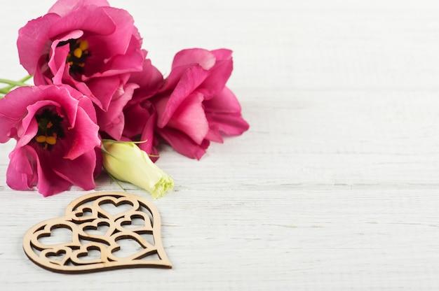 Flores eustoma roxas rosa e coração de madeira