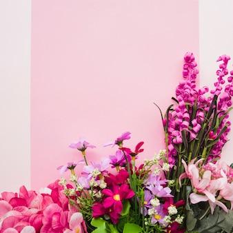 Flores falsificadas coloridas decorativas contra o fundo cor-de-rosa