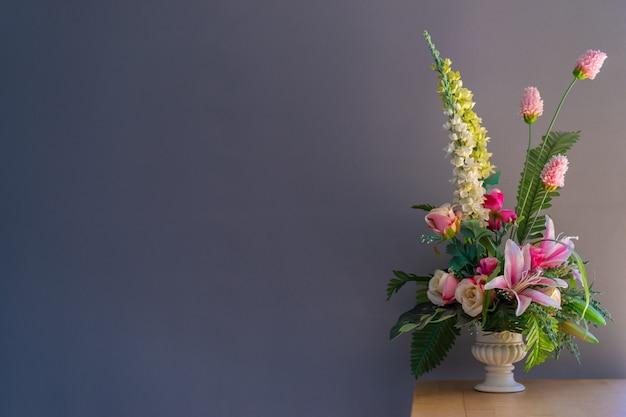 Flores falsificadas em um vaso na mesa de madeira com fundo cinza