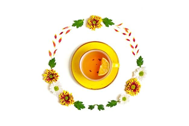 Flores, folhas verdes e xícara de chá quente com limão