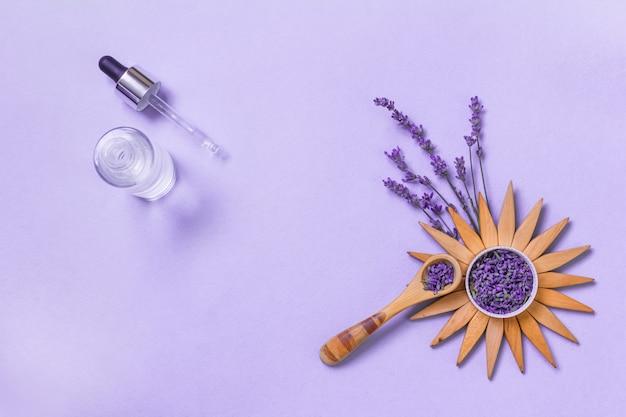 Flores frescas de lavanda amarradas em cachos e óleos essenciais em frascos decorativos. cosméticos naturais.