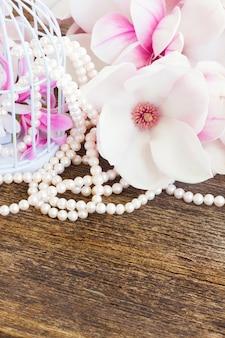Flores frescas de magnólia com joias de pérolas na mesa de madeira