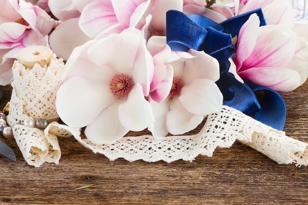 Flores frescas de magnólia com pérolas e renda vintage na mesa de madeira