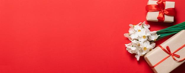 Flores frescas de narcisos brancos com caixa de presente no vermelho