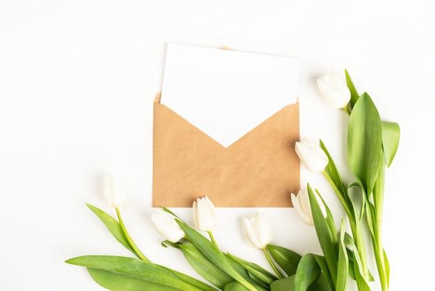 Flores frescas de tulipas brancas e cartão em branco com vista superior do envelope no fundo branco