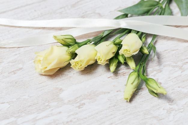 Flores frescas do eustoma branco no desktop de madeira claro com espaço da cópia.