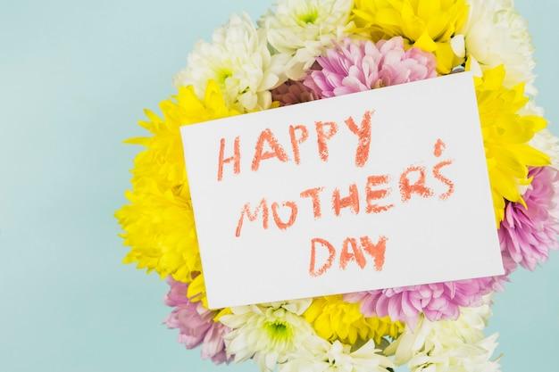Flores frescas e brilhantes com papel com feliz dia das mães título