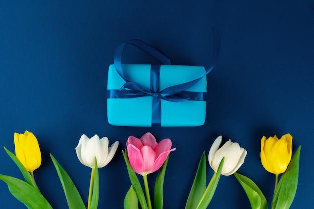 Flores frescas e caixa de presente com fita em fundo azul clássico