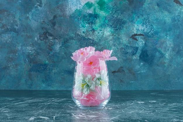 Flores frescas e elegantes em um copo, na mesa azul.
