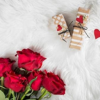 Flores frescas e presentes com corações de ornamento na colcha de lã