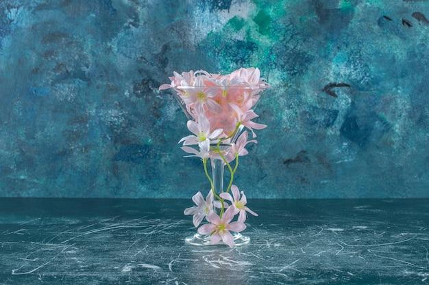 Flores frescas em um copo, sobre fundo branco.