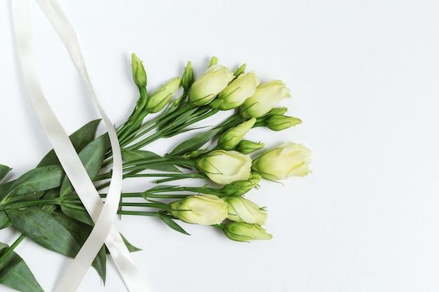 Flores frescas eustoma brancas sobre fundo branco claro, com espaço de cópia