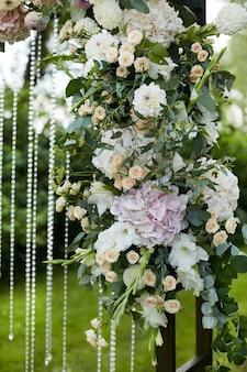 Flores frescas exóticas no arco de casamento de madeira ao ar livre.