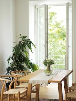 Flores frescas no vaso de vidro que está em uma tabela de madeira no interior branco da sala de jantar com tapete oriental. design de interiores em estilo minimalista.