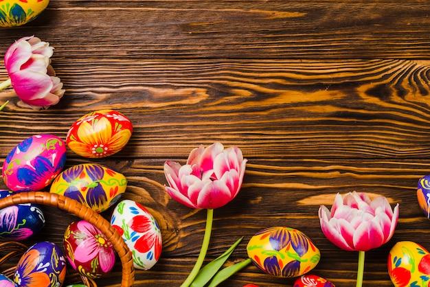 Flores frescas perto de conjunto de ovos de páscoa
