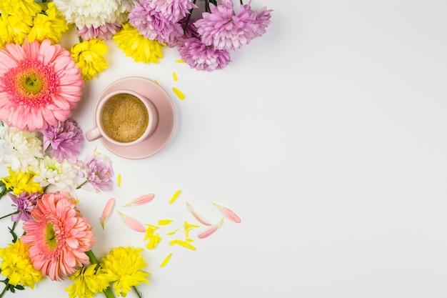 Flores frescas perto de copo de bebida e pétalas