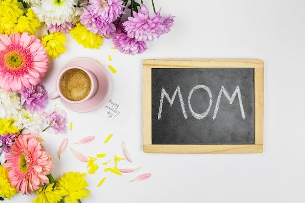 Flores frescas perto de copo de bebida, lousa com palavras de mãe e pétalas