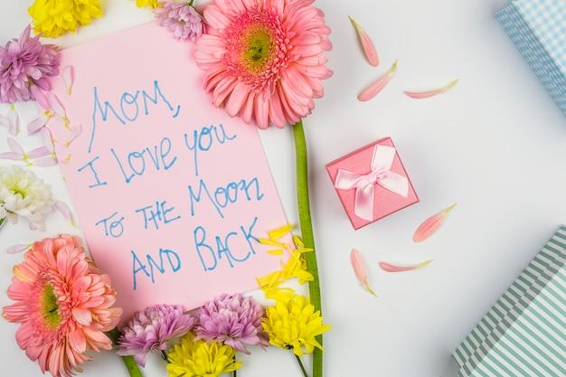 Flores frescas perto de papel com palavras, pétalas e caixas de presentes