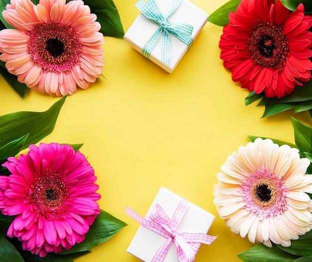Flores gerbera e caixas de presente em uma mesa amarela. vista do topo